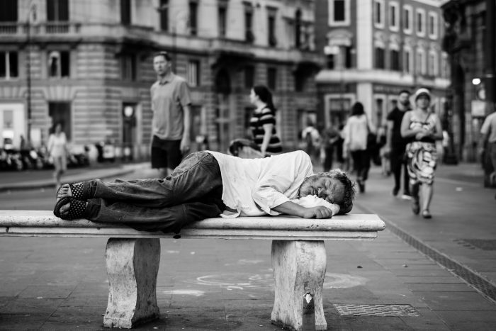 man sleeping at the middle of the street