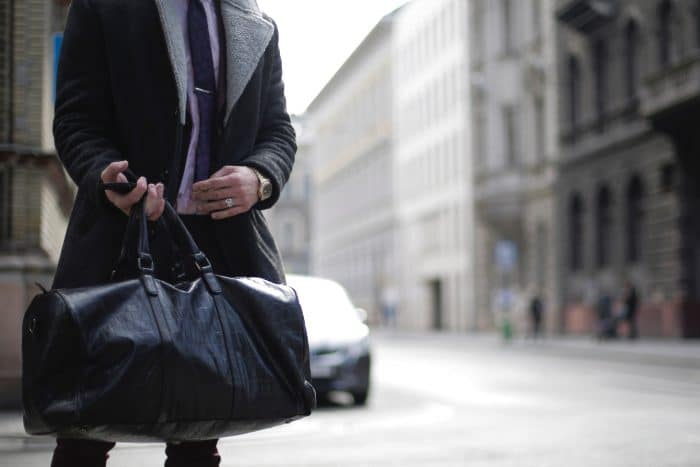 person-in-black-trench-coat-holding-black-leather-travelbag-3888023